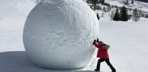 Criança agasalhada com uma calça preta, casaco vermelho e uma touca de frio vermelha, branca e azul. Ele está empurrando uma bola de neve gigante em um local que faz muito frio. O intuito dessa imagem é representar o Efeito Bola de Neve da matéria acumulada.