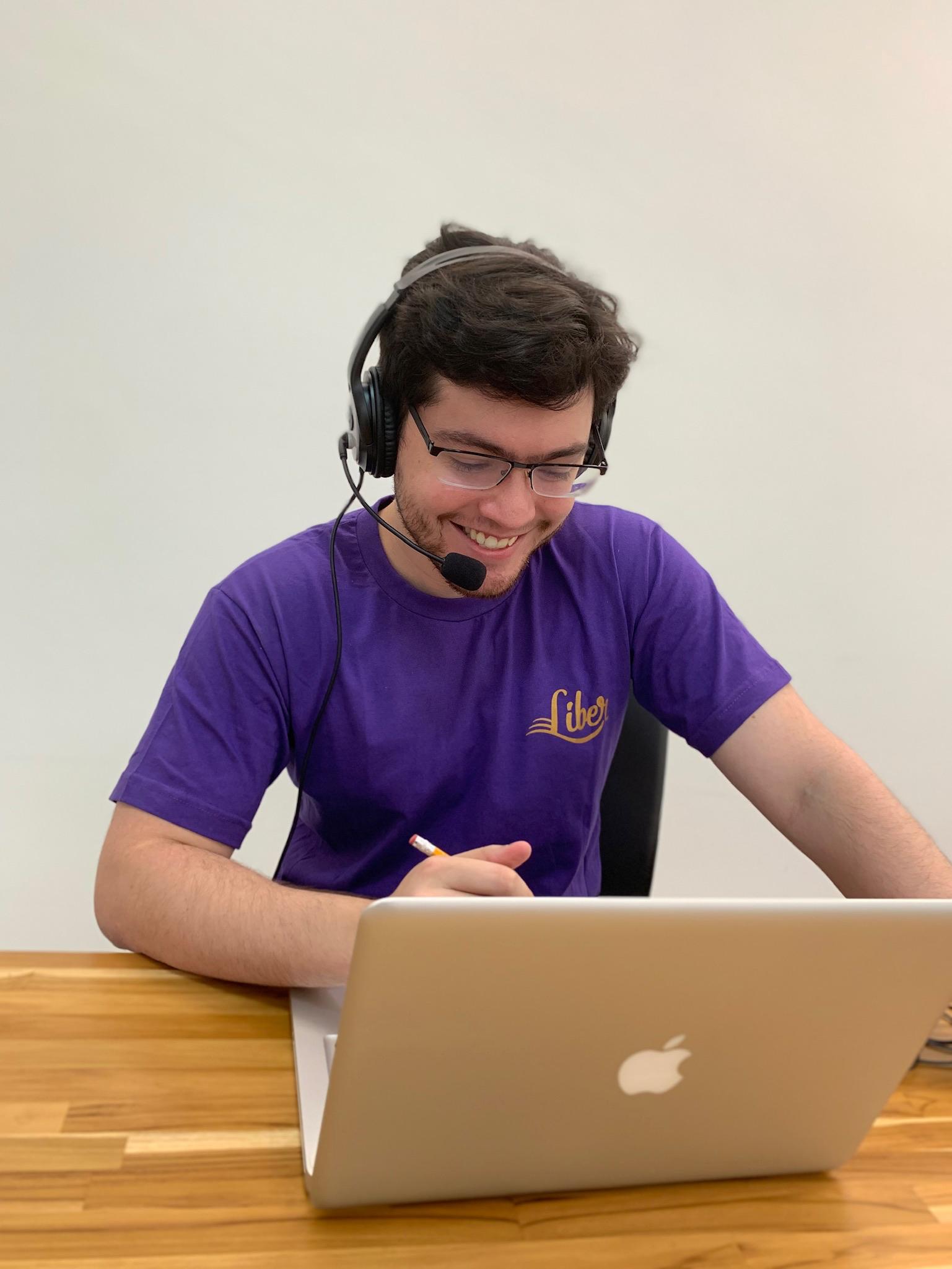 Tutor vestindo uma blusa roxa, segurando um lápis e usado um fone de ouvido com microfone. Ele está dando uma aula online com seu notebook que está apoiado em uma mesa de madeira.