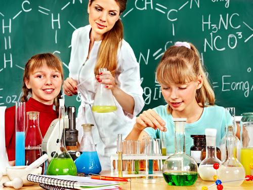 Laboratório de química com lousa, tubos de ensaio com substâncias dentro, cadernos, canetas, microscópios e outros recipientes e elementos químicos. Estão no ambiente duas alunas de, aproximadamente, 12 anos, e uma professora. Elas estão testando experiências e mexendo com os objetos.
