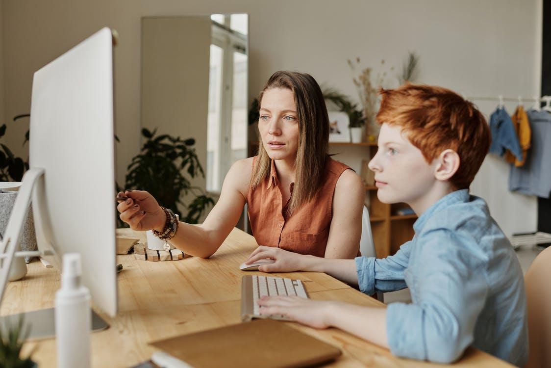 Mãe usando uma blusa sem manga marrom ajudando o seu filho de, aproximadamente, 13 anos, que está usando uma camisa jeans de botão. Eles estão estudando em casa, utilizando um computador que está na superfície de uma mesa de madeira.