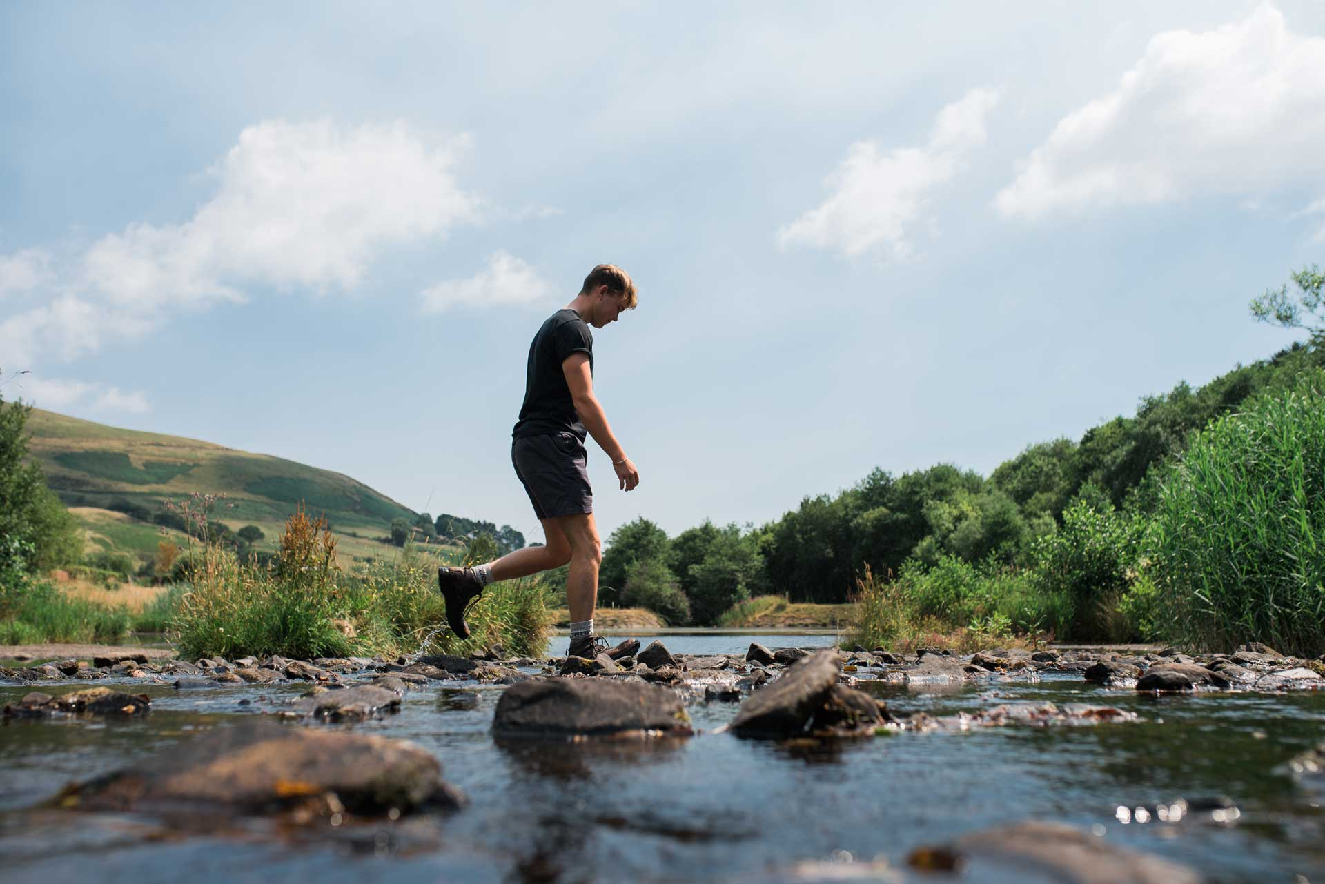 A young adult male crossing the stepping stones of a river