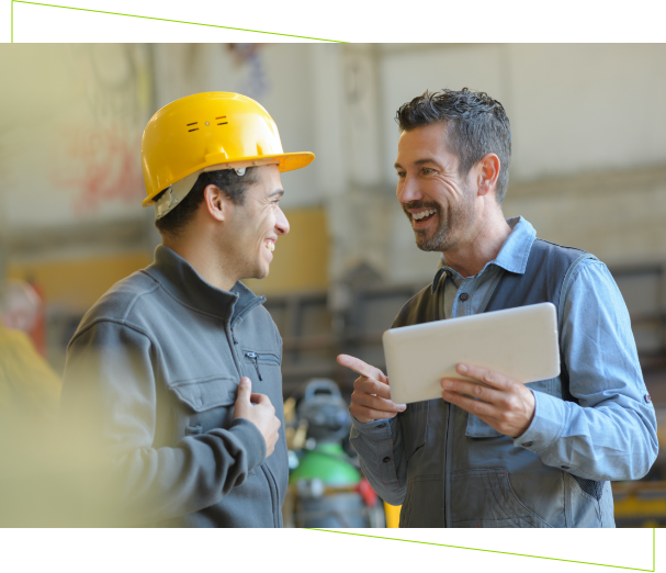 Two construction workers discussing work while holding tablet.