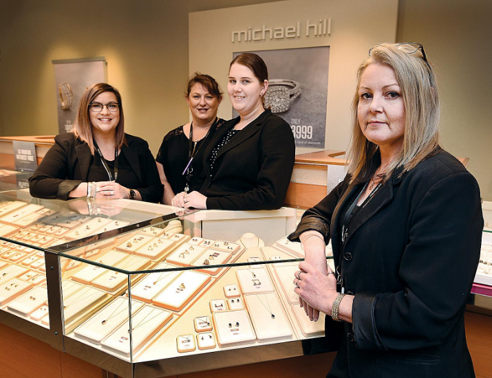 Team of jewellers standing next to display glass