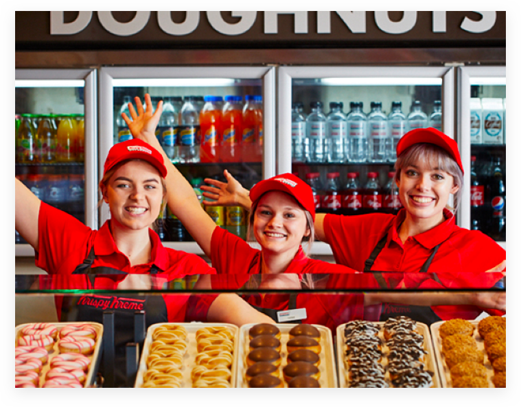 Krispy Kreme staff showing a variety of donuts