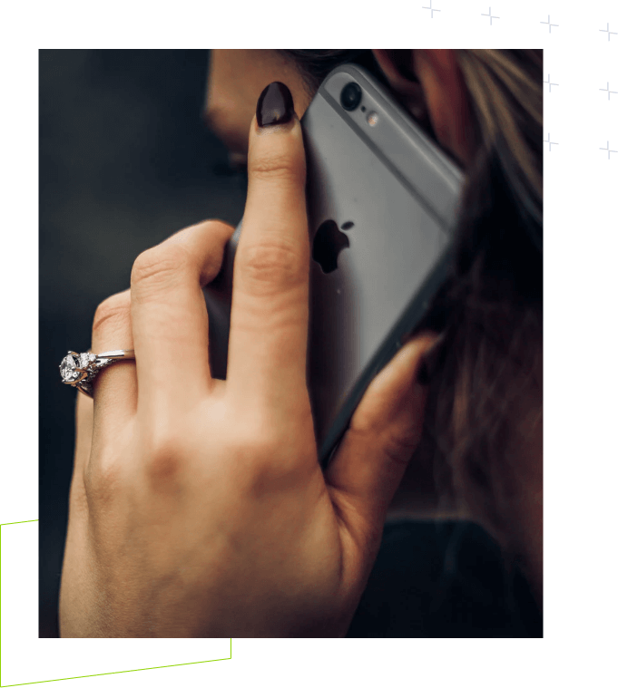 Hand with dark nail polish and engagement ring holding a phone to her ear.