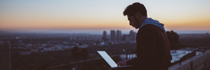 Man working remotely outside with a laptop