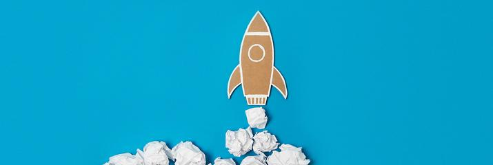 Cardboard rocket with scrunched up paper on blue background