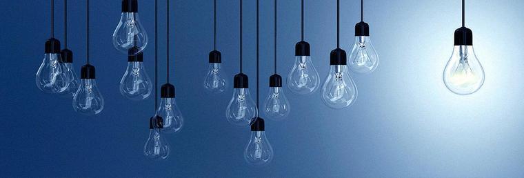 hanging lightbulbs with one illuminated