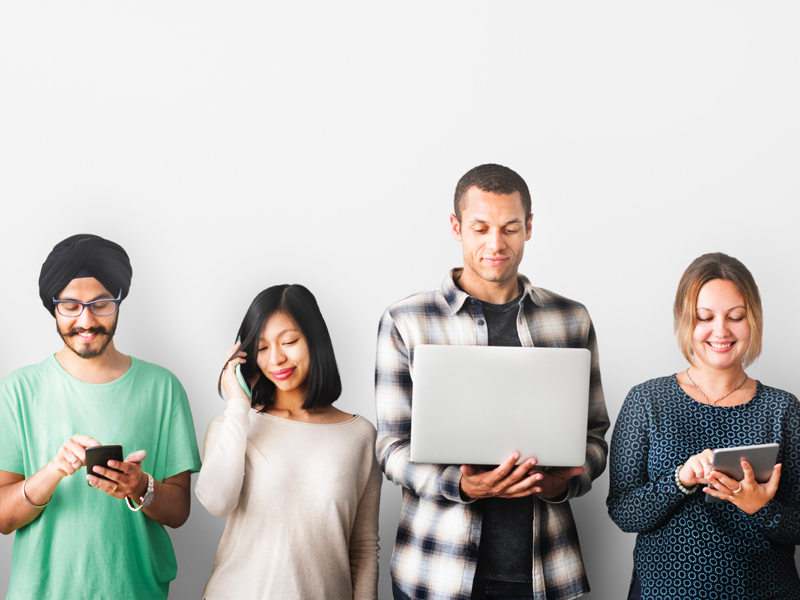 People on devices in front of grey wall