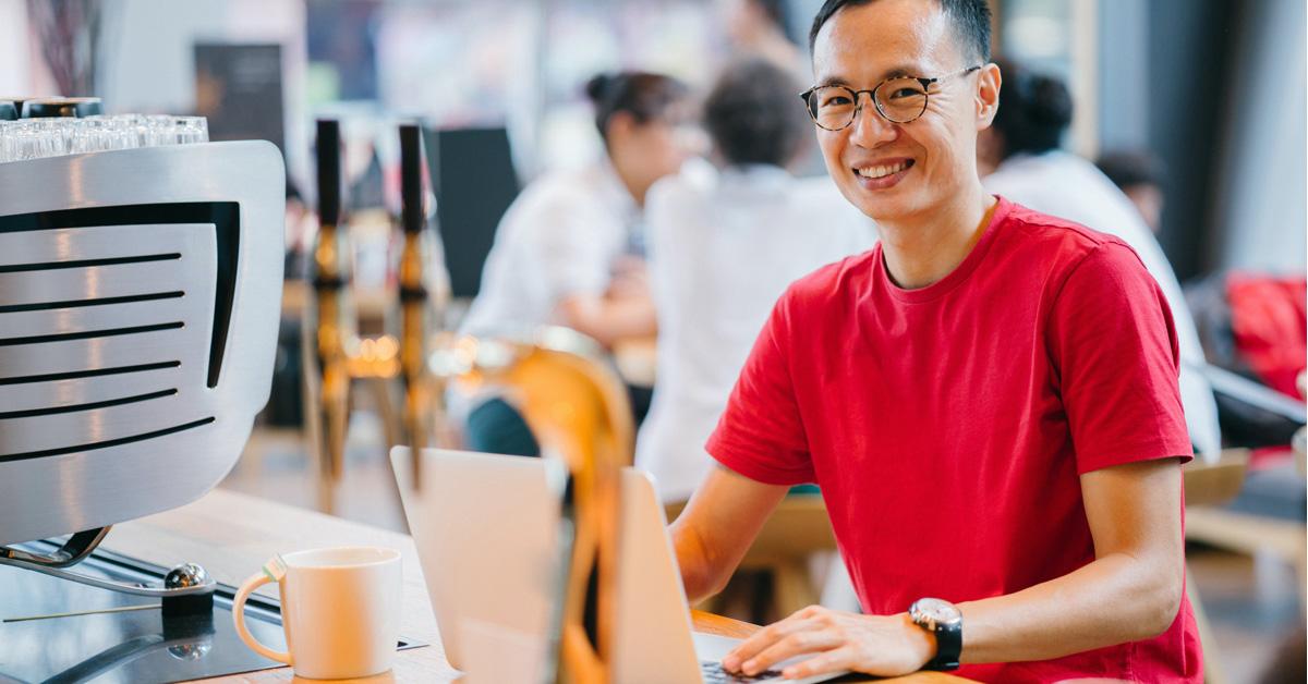 Asian man at cafe working on laptop smiling at camera