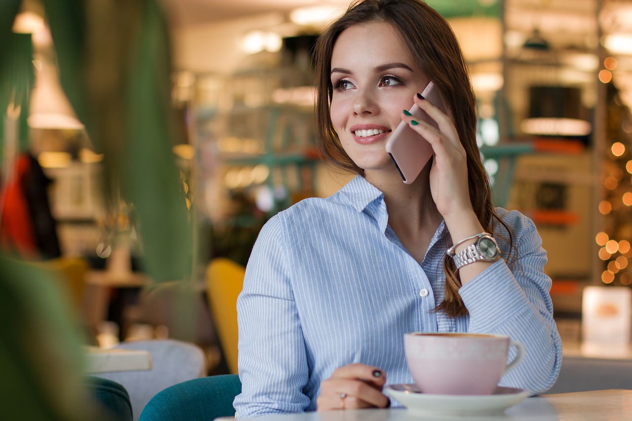 Woman at cafe, drinking coffee and talking on phone