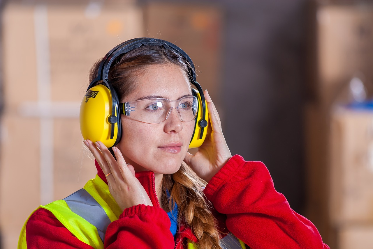 Blue collar worker woman with safety goggles and earmuffs