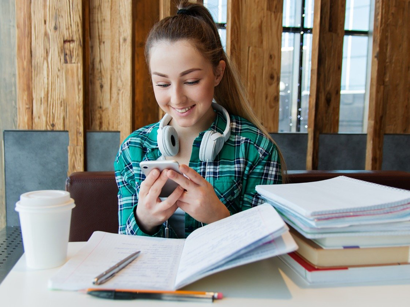 Young woman on phone with notebooks on desk