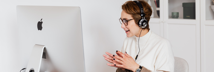 Woman at desk on video call with headphones
