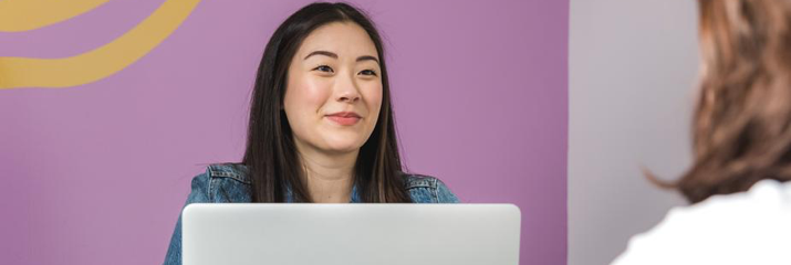Asian woman on laptop with purple background