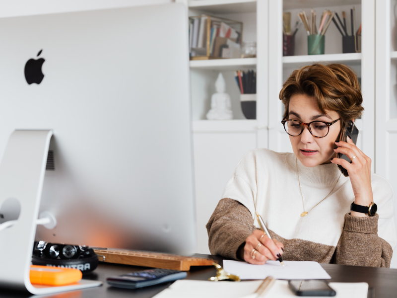 Woman working at desk with iMac on her phone taking note