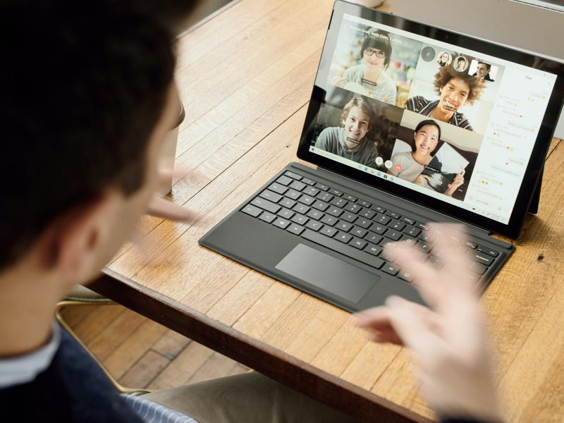 Man looking at laptop in zoom meeting