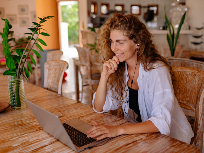 Woman working at table with laptop and headphones