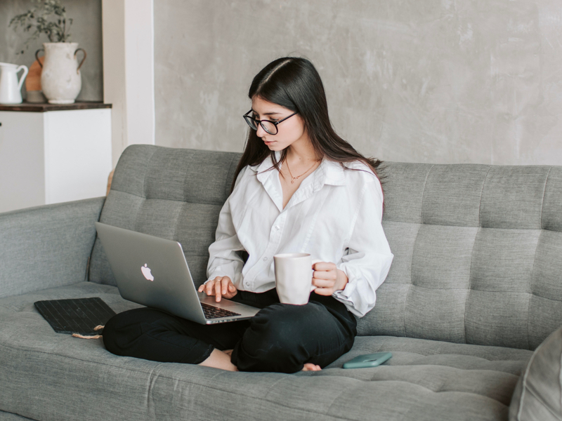 Woman sitting on couch drinking tea and working on laptop