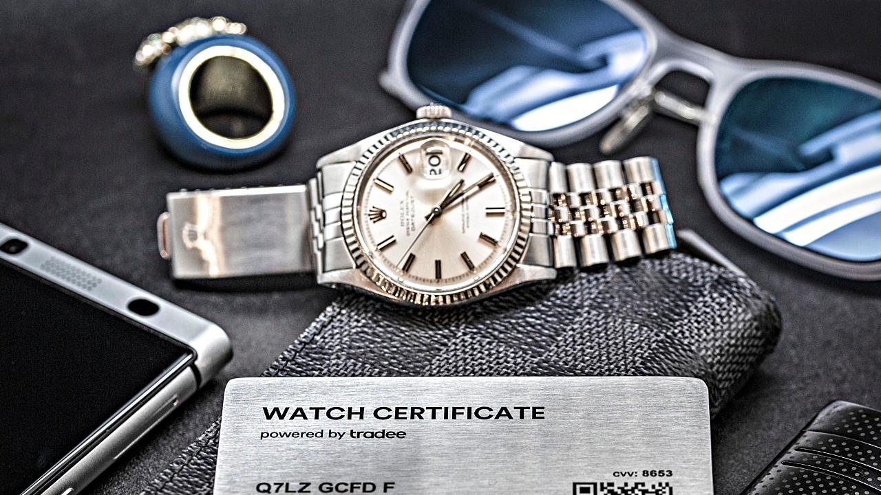 Rolex Datejust avec un Watch Certificate, et en arrière plan une bague et une paire de lunettes