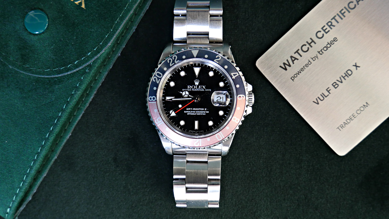 Rolex GMT-Master 2 avec à sa droite un Watch Certificate Steel et à sa gauche une pochette Rolex