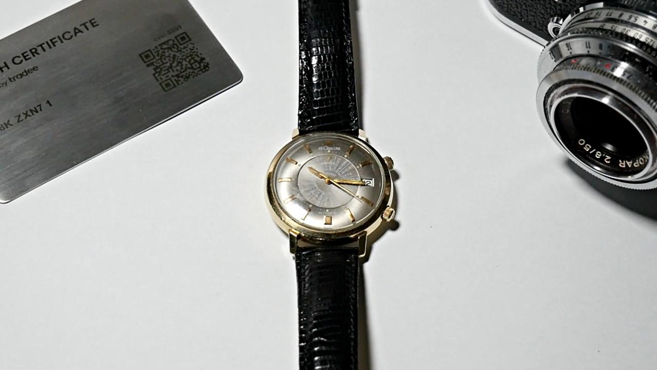 Jaeger-LeCoultre Memovox sur fond blanc avec à sa gauche un Watch Certificate Steel et à sa droite un appareil photo