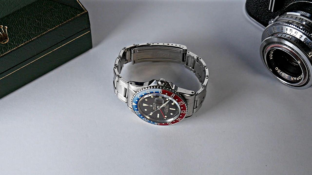 Rolex GMT-Master 1675 sur un fond blanc, avec à sa droite un boitier Rolex et à droite un appareil photo
