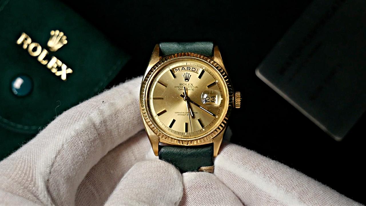Rolex Day-Date 1803 dans les mains gantées d'un horloger, avec en arrière plan une pochette Rolexw