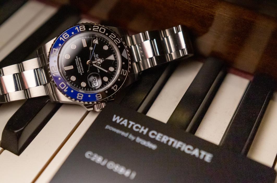 Photo d'une Rolex GMT-Master avec son Watch Certificate Black sur un piano