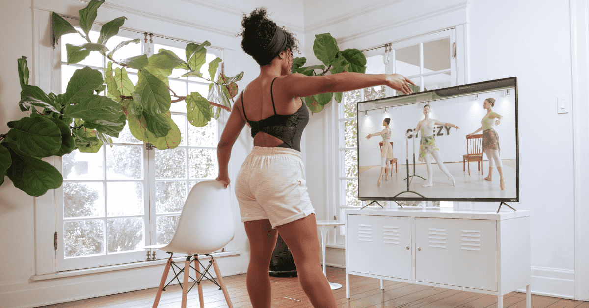 Woman taking ballet class on her television at home