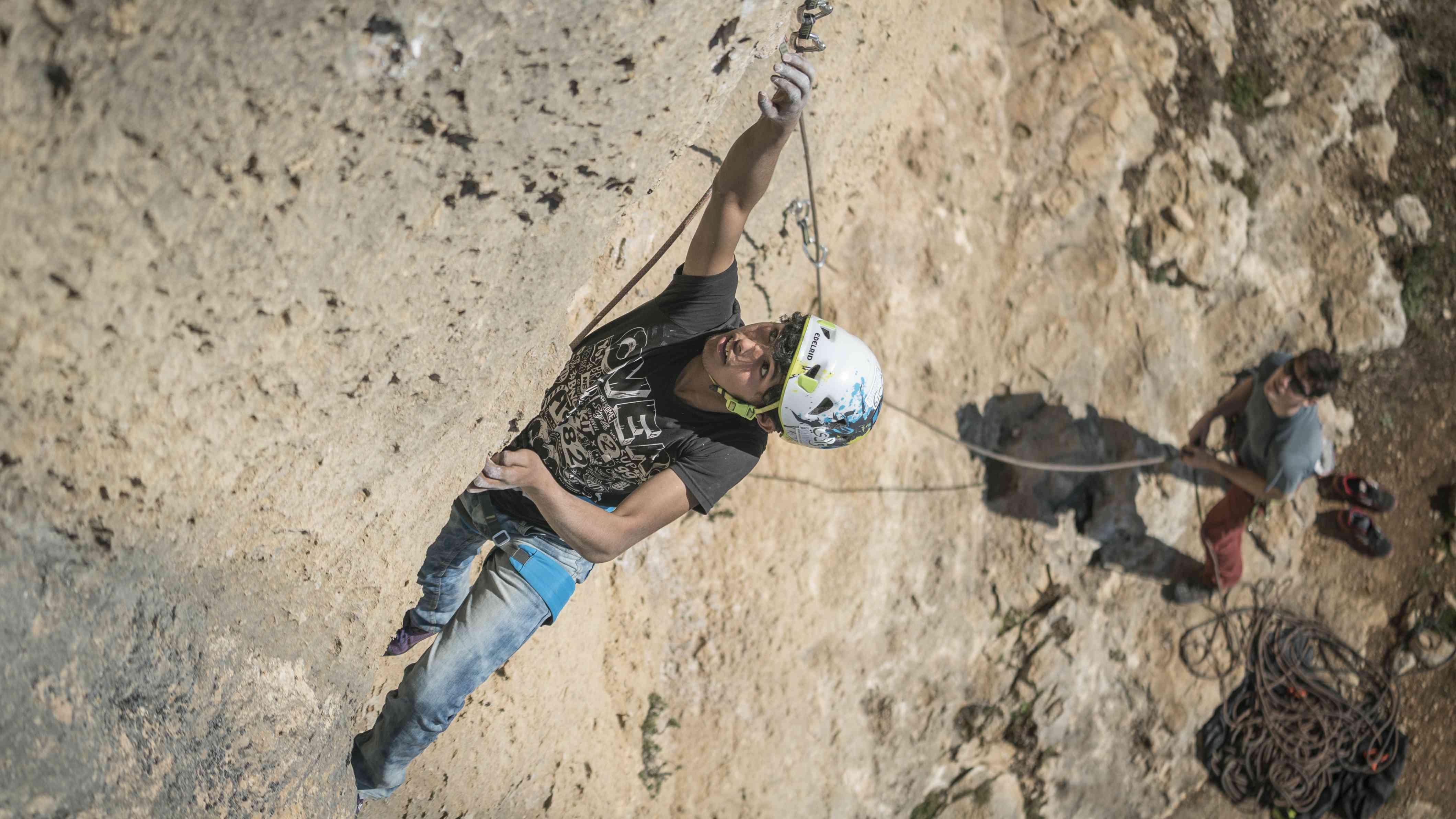 Prendere il quickdraw mentre si arrampica in Cisgiordania