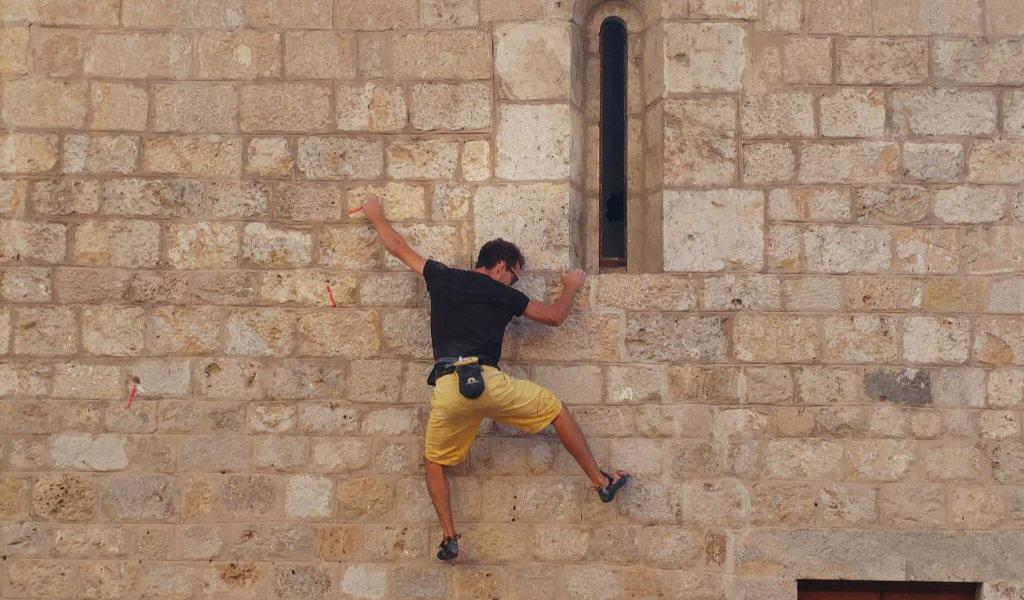 Una persona che si arrampica su un edificio durante lo Slow Travel Fest del 2018 a Camaiore