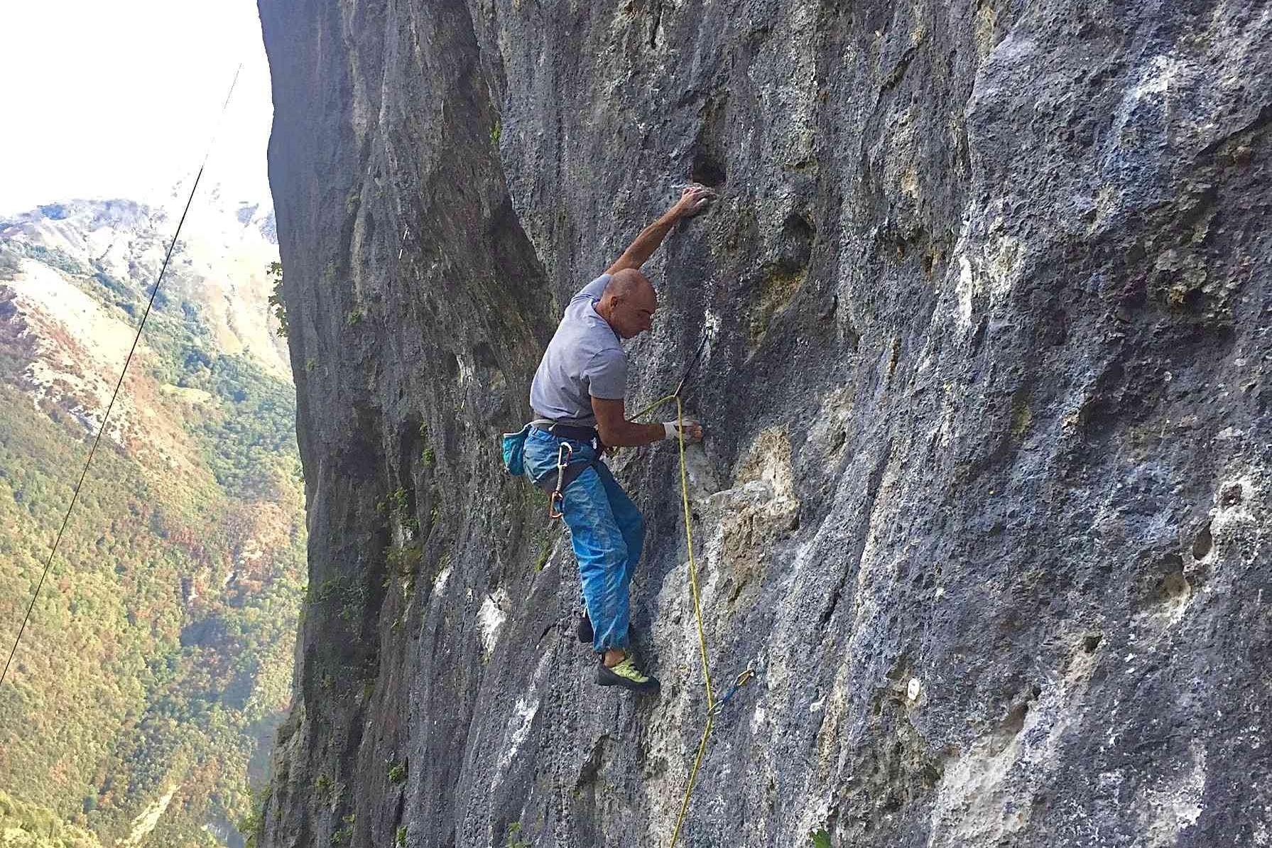 Un primo piano di un arrampicatore su una via verticale a Camaiore