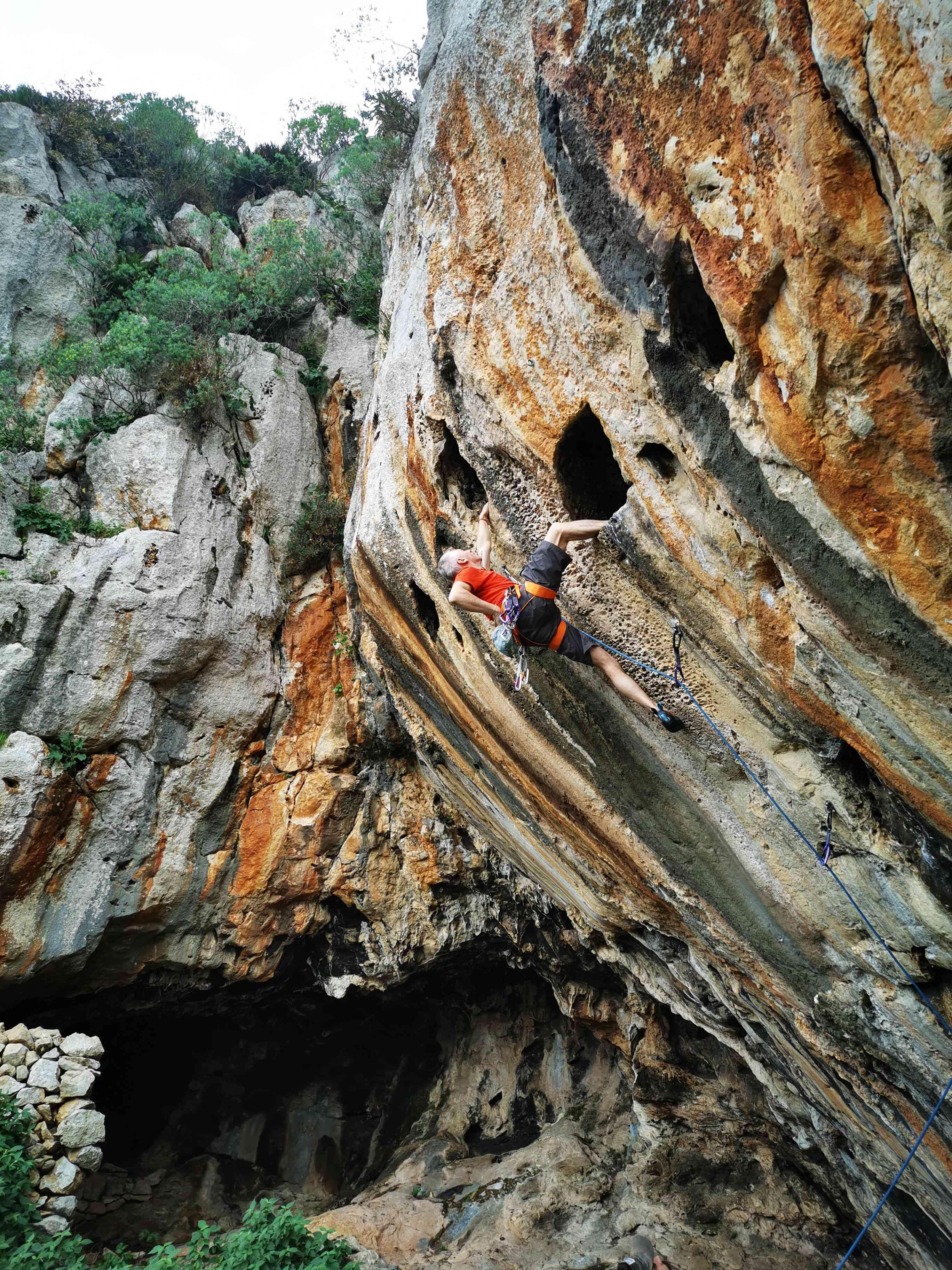 longshot di un tallone scalatore che si aggancia in un buco su una scogliera di calcare arancione e nero striato
