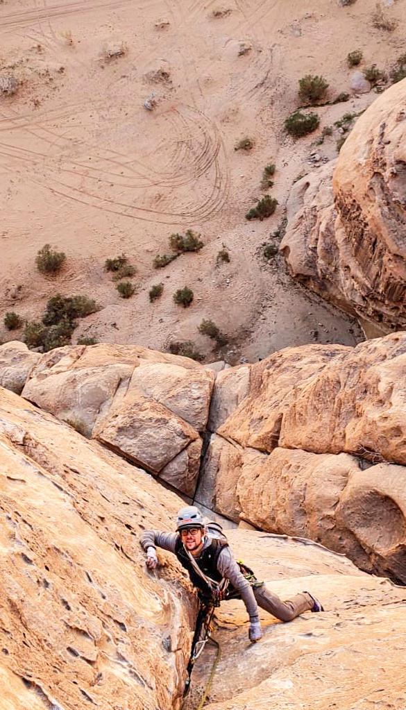 Un arrampicatore in primo piano guarda in alto mentre infila il suo pugno nella fessura