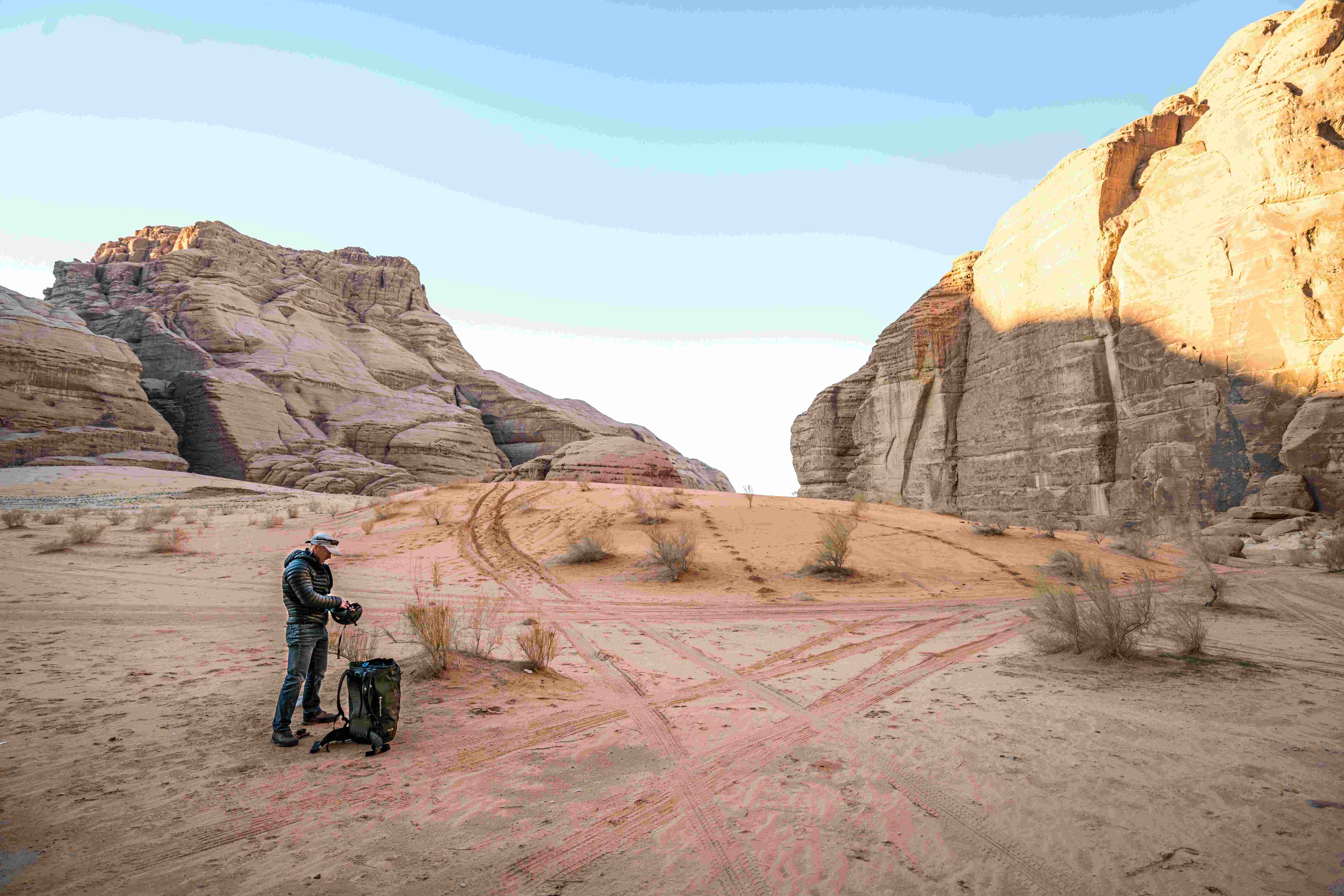 Uno scalatore con uno zaino in piedi in primo piano con le cime di arenaria sullo sfondo