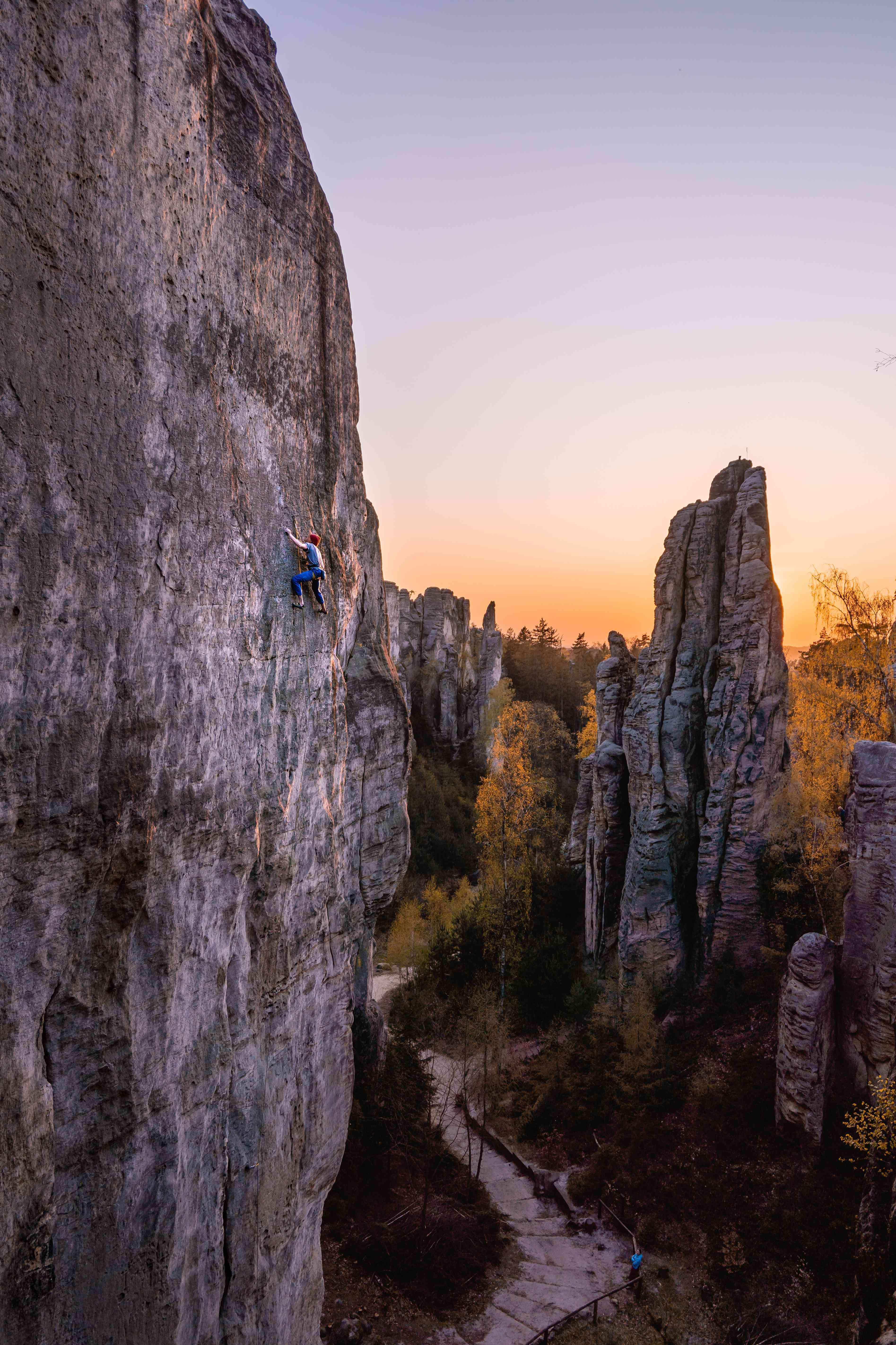 Longshot di una persona che si arrampica su una scogliera al tramonto a Cesky Raj