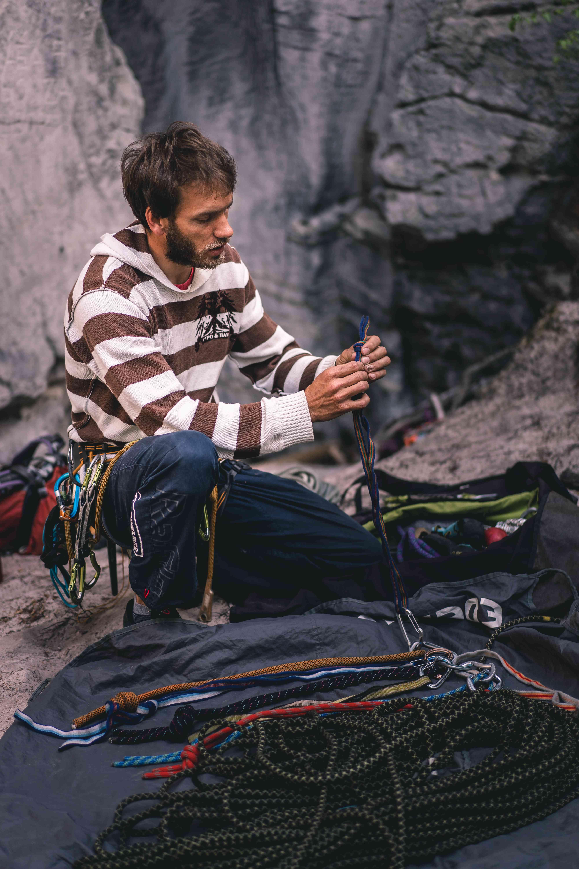 Primo piano di una persona accovacciata che ispeziona un'imbracatura. Indossano un'imbracatura con molte imbracature che pendono da essa