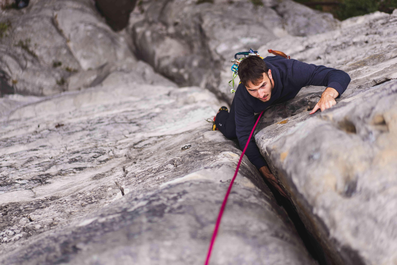 Ripresa ravvicinata di uno scalatore in cima a una via, con il braccio incastrato in una fessura