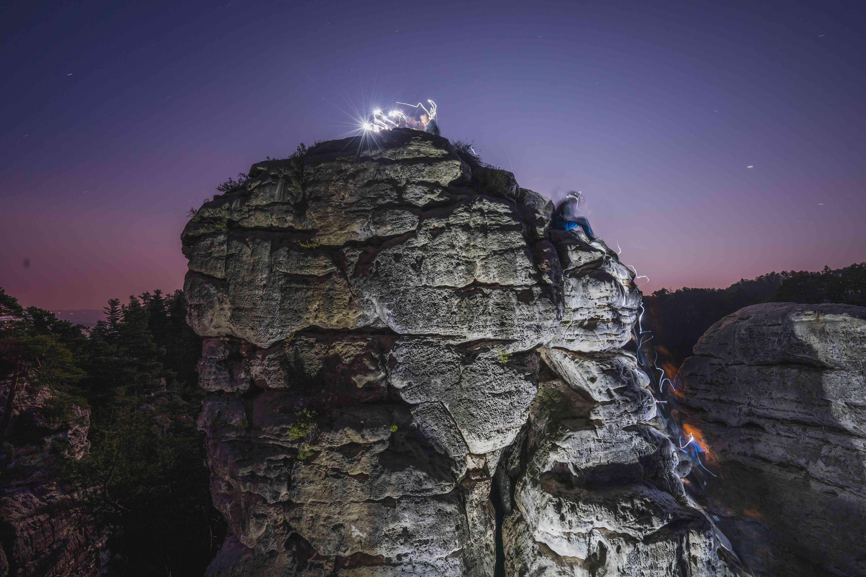 una casa seduta sulla cima di una scogliera di notte