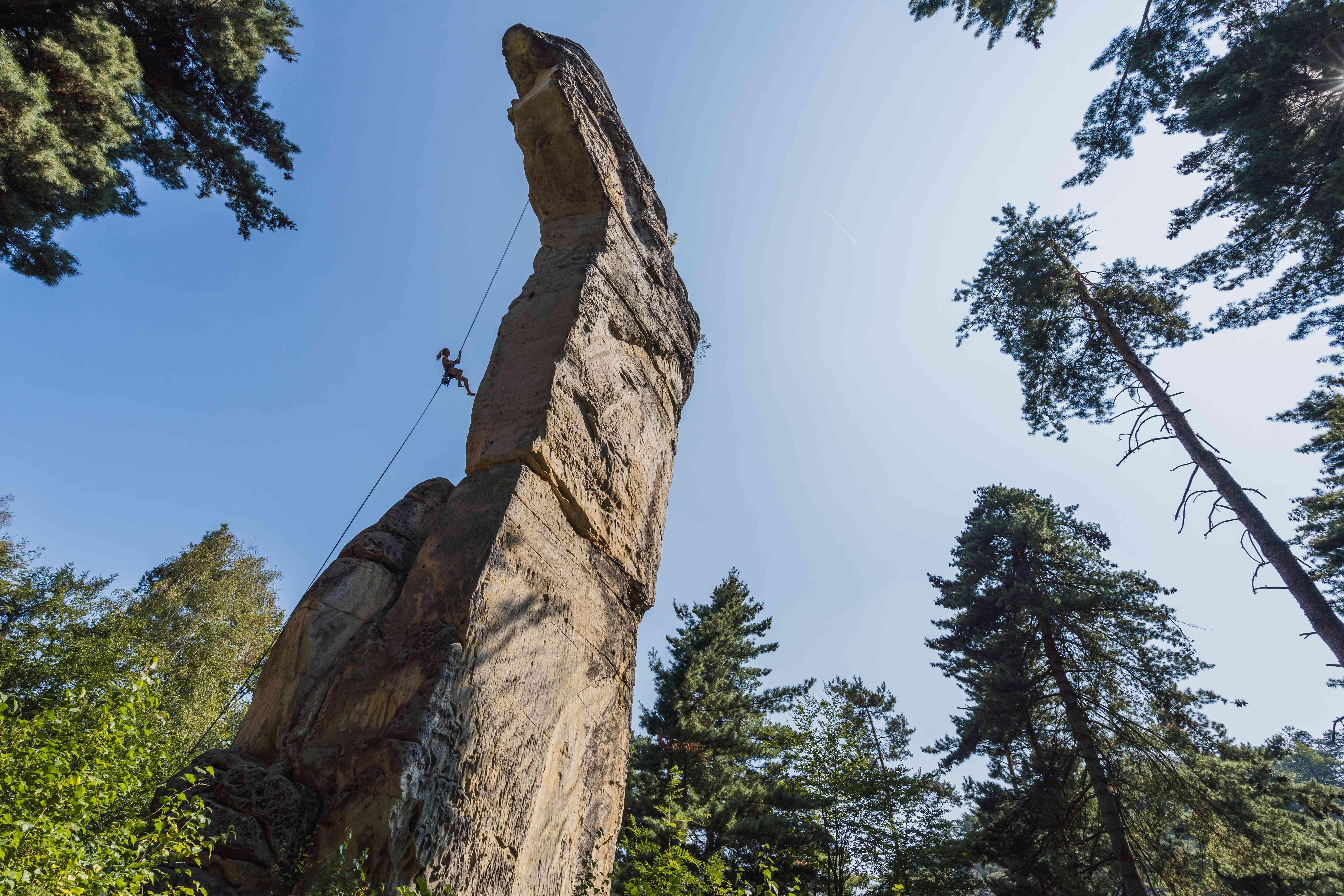 Foto di uno scalatore che si cala in corda doppia da una torre di roccia lunga e sottile nella Repubblica Ceca