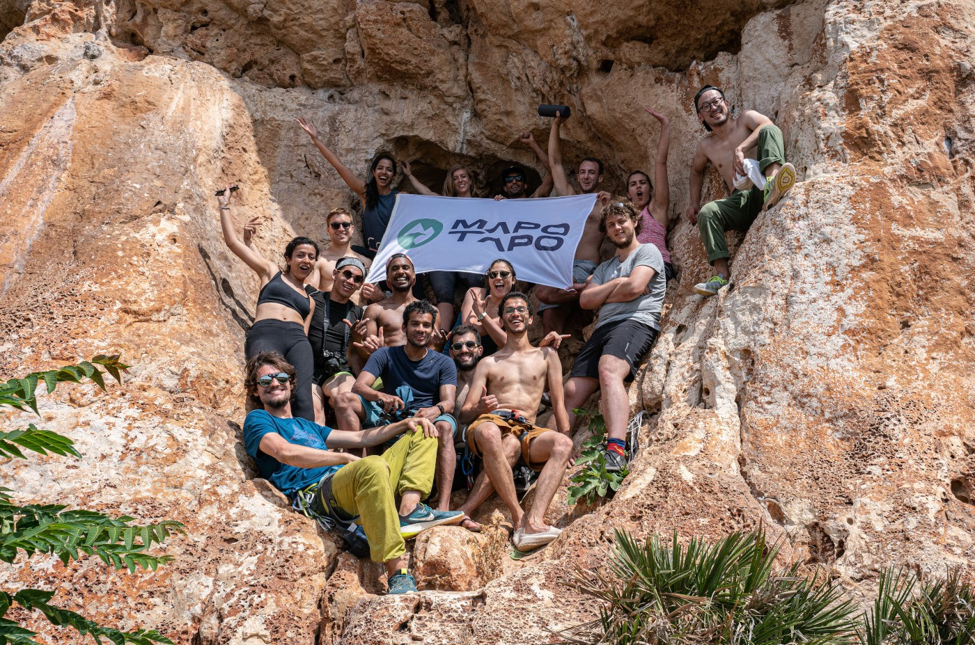 A  group of rock climbers smiling and waving at the camera while holding a  Mapo Tapo banner