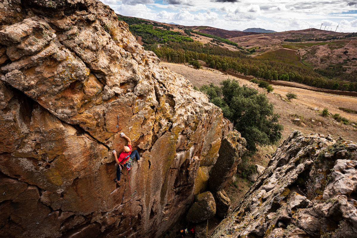 A rock climber approaching the anchors while at a crag in Sicily