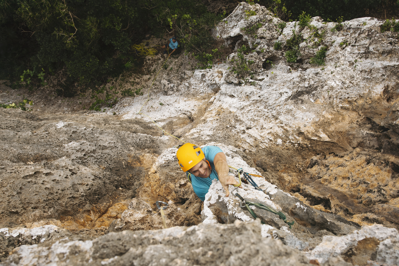 Juan trad climbing in Jamaica, protecting himself with slings