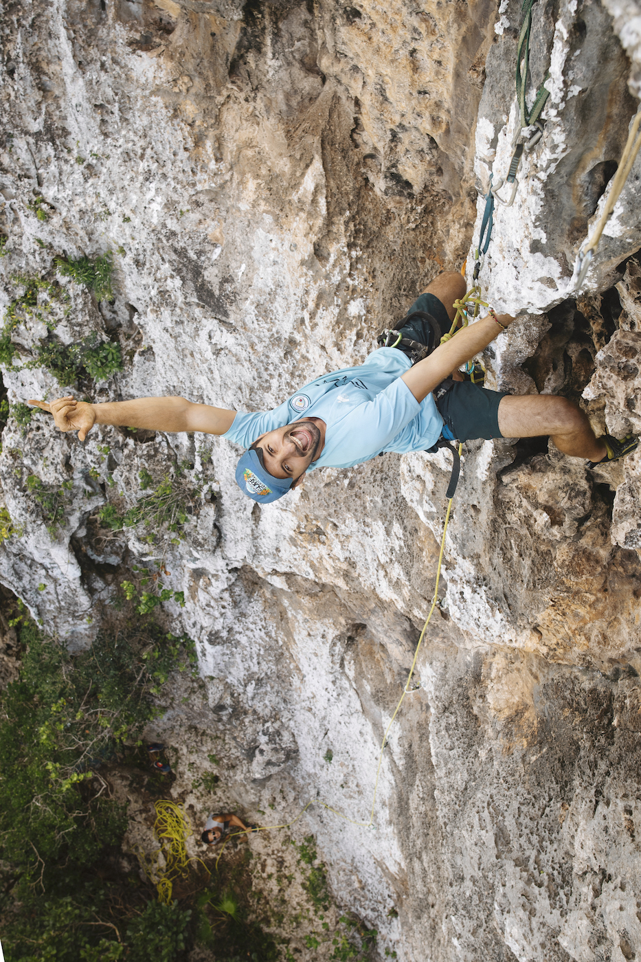 A person smiles at the camera while rock climbing in Jamaica