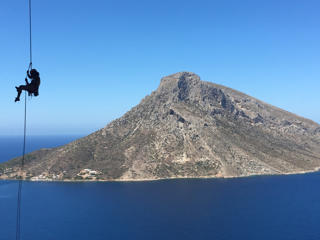 A climber rapelling off Grande Grotta, Kalymnos, with a view of Leros in the background