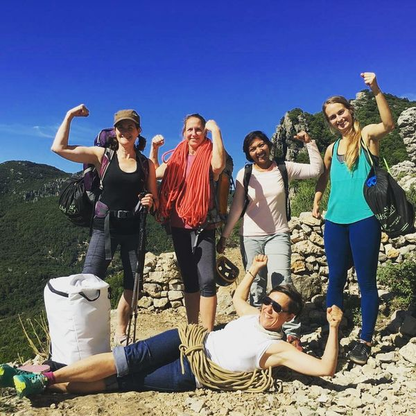 women climbers at the crag in Sardinia, flexing their biceps