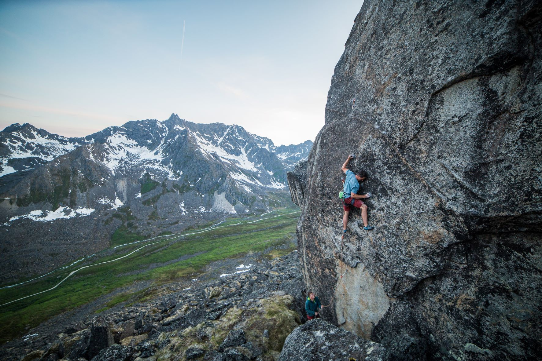 A person rock climbing in Hatcher Pass, Alaska in the foreground, with mountains in the backgroundth snow