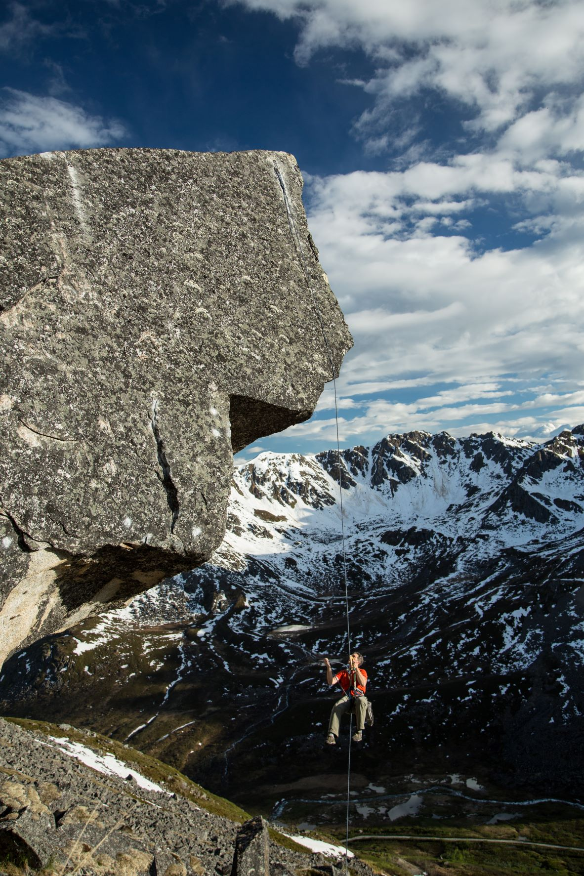 A climber rapeling of a route in Hatcher Pass in the foreground, with a mountain range in the background