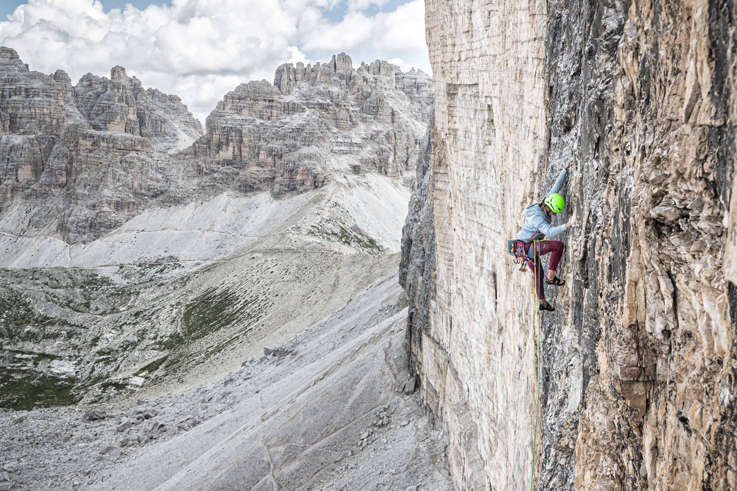 Eline Le Menestrel looks down at her foot while climbing on a bigwall in the Dolomites. The mountains are in the background